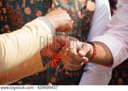 A Man Tying Friendship Band On Wrist Of Another Man. Male Rakhi Or Rakshabandhan Concept Image Of In