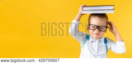 Banner Funny Preschool Child Boy In Glasses With Book On Head And Bag On Yellow Background Copy Spac