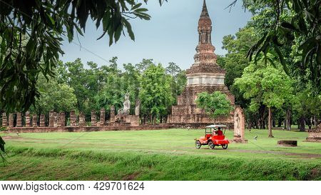 The Scenery Of The Red Electric Car Travel Past The Ancient Ruined Structure At Sukhothai National P