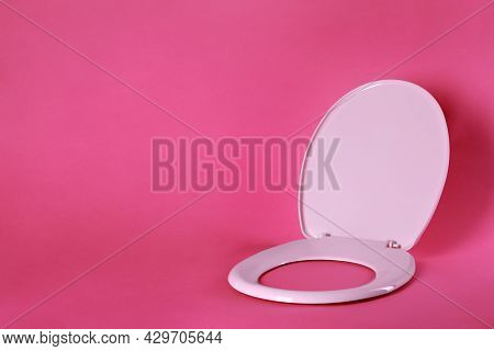 New Plastic Toilet Seat On Pink Background, Space For Text