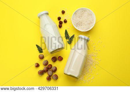 Vegan Milks, Hazelnuts And Rice On Yellow Background, Flat Lay