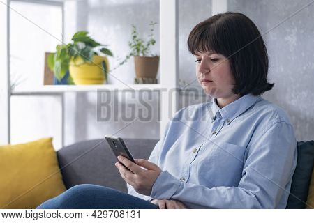 Serious Young Woman Is Sitting On The Couch With A Phone In Her Hands. Smm Manager. Business Woman S