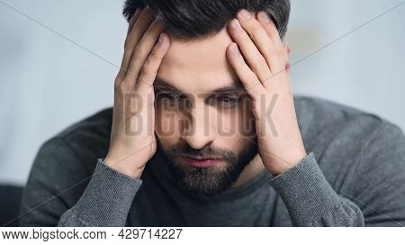 Dissatisfied And Bearded Man Touching Forehead With Hands.