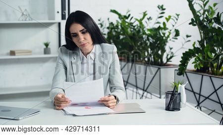 Dissatisfied Businesswoman Looking At Document In Office.