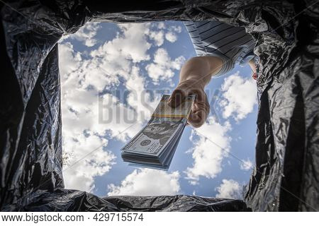 Throwing Away Dollars In Trashcan. Getting Rid Of Excess Cash, Switching To Non-cash Payment. The Co