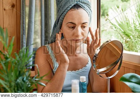Skincare Routine. Middle Age Woman Touching Her Face With Cloth Moisturizing Mask And Looking In Mir