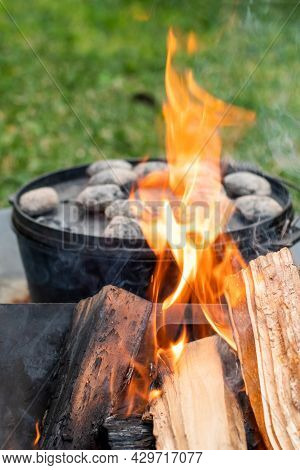 Dutch Oven Camp Cooking With Coal Briquettes Beads On Top. Campfire. Camping Life