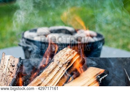 Dutch Oven Camp Cooking With Coal Briquettes Beads On Top. Campfire