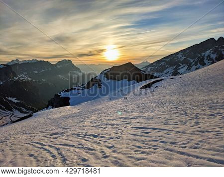 Ski Tour At Sunrise, Ski Mountaineering Ski Touring On A Mountain Peak In The Swiss Alps. Clariden.