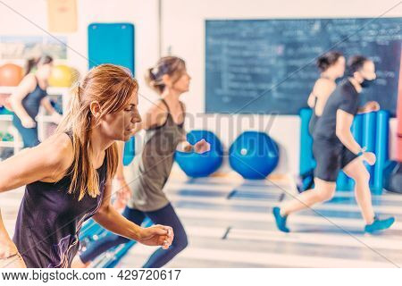 Side View Of Women Doing Aerobic Exercises In Health Club