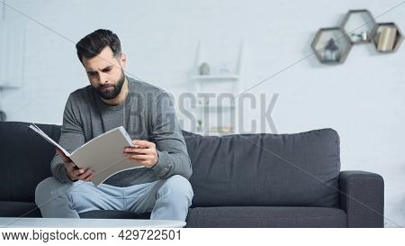 Dissatisfied Man Looking At Folder While Sitting On Sofa In Living Room.