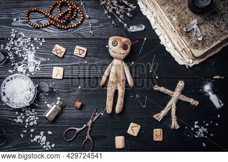 Voodoo Doll With Pins Surrounded By Ceremonial Items On Black Wooden Table, Flat Lay