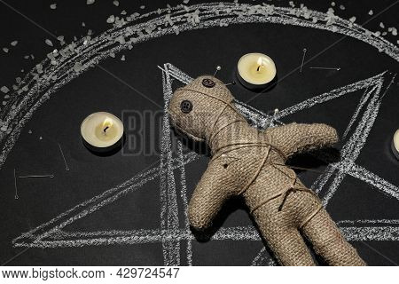 Voodoo Doll Pierced With Pins And Candles In Pentagram On Table