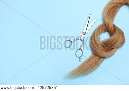 Professional Hairdresser Scissors And Hair Strand On Turquoise Background, Flat Lay With Space For T
