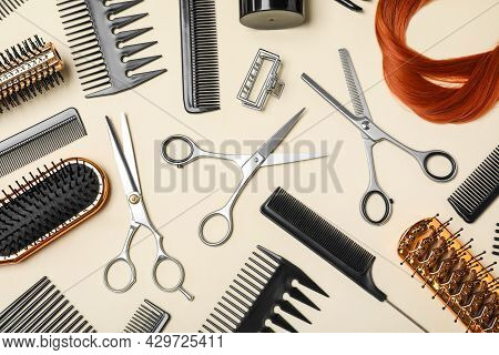 Flat Lay Composition Of Professional Scissors, Hair Strand And Other Hairdresser's Equipment On Beig
