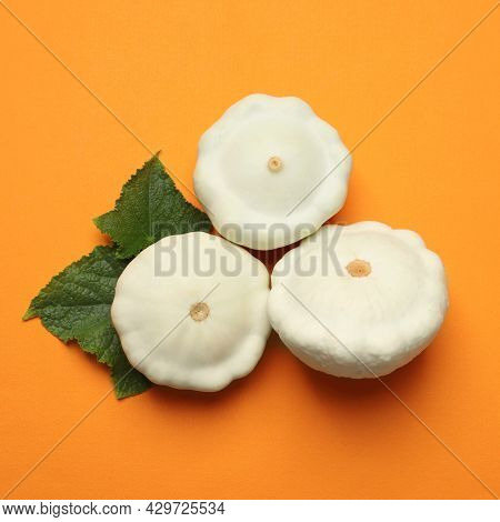Fresh Ripe Pattypan Squashes With Leaves On Orange Background, Flat Lay