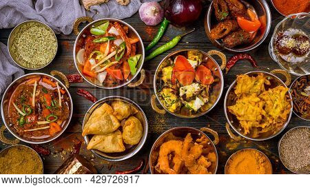 Assorted Indian Food Set On Wooden Background. Dishes And Appetisers Of Indeed Cuisine, Rice, Lentil
