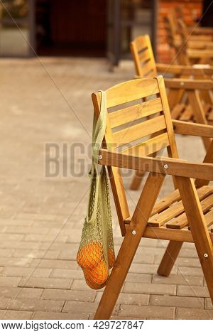 Rattan Cafe Chair With Net Bag With Oranges Fruits. Street Cafe.