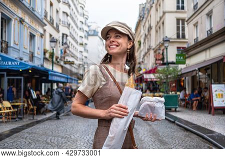 Attractive girl with French baguette on the street