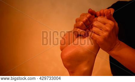 Partial View Of Masseur Massaging Leg Of Barefoot Woman On Massage Table.