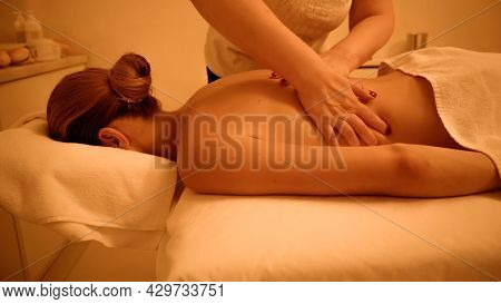 Young Woman Receiving Back Massage From Professional Masseur In Spa Salon.