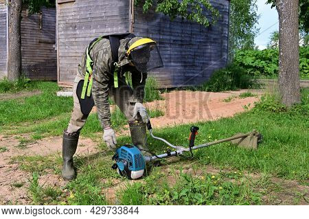 Worker In Special Protective Clothing With Lawn Mower In His Hands Mows Grass. Trimer Mows Lawn. Law