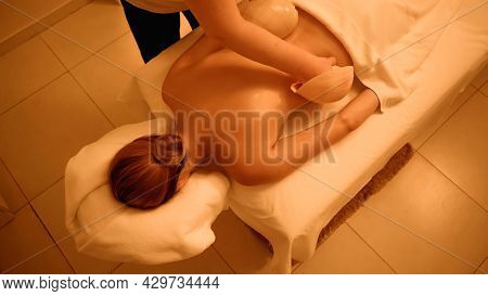 High Angle View Of Professional Masseur Massaging Young Woman With Sea Shells In Spa Salon.