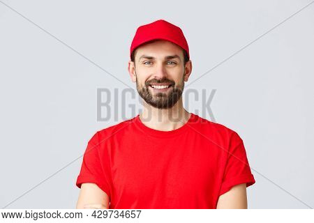 Online Shopping, Delivery During Quarantine And Takeaway Concept. Handsome Bearded Courier In Red Un