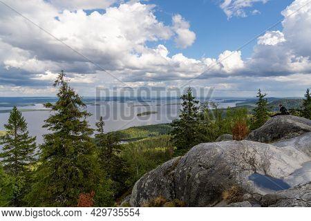 Koli, Finland - 30 July, 2021: Female Hiker Enjoys A Break And The View From Koli Mountain Peak In T