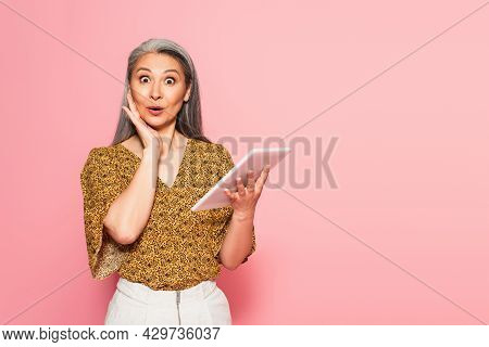 Astonished Woman With Digital Tablet Touching Face And Looking At Camera Isolated On Pink