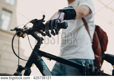 Young Disabled Man With Artificial Prosthetic Hand In Casual Clothes Riding Bike