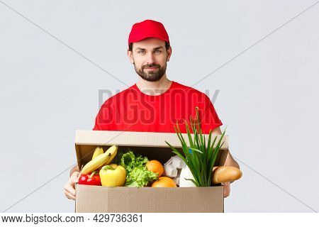 Groceries And Packages Delivery, Covid-19, Quarantine And Shopping Concept. Handsome Courier In Red