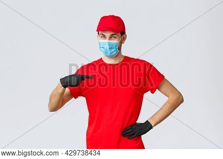 Covid-19, Self-quarantine, Online Shopping Concept. Confident Smiling Delivery Guy In Face Mask, Glo