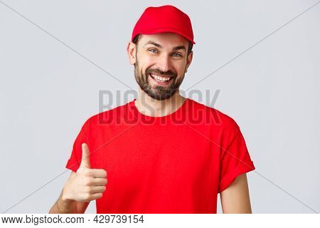 Online Shopping, Delivery During Quarantine And Takeaway Concept. Friendly, Cheerful Courier In Red