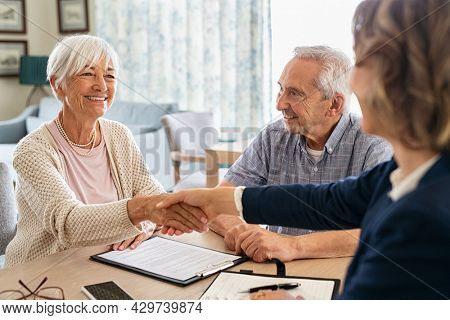 Happy old woman shaking hands with medical adviser for health insurance while sitting at home. Senior couple signing deal for insurance with financial advisor after retirement.