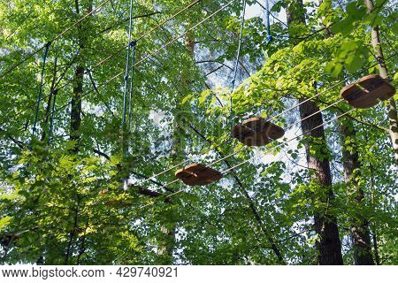 Fragment Of The Obstacle Course In The Rope Park At A Height In The Foliage Of The Trees. Outdoor Ac