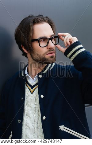 Fashionable Man In Pullover And Jacket Adjusting Eyeglasses While Looking Away