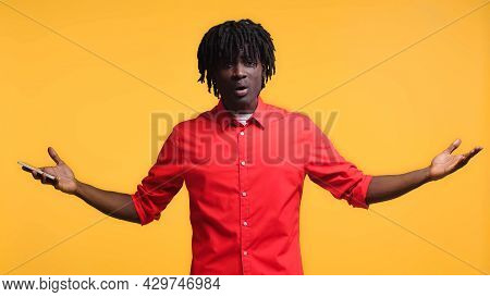 Irritated African American Man Holding Smartphone And Gesturing Isolated On Yellow