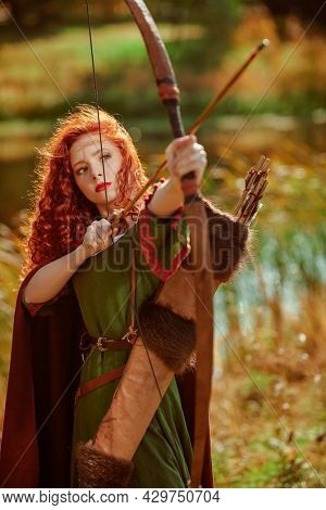A beautiful red-haired girl archer of the Middle Ages aiming with a bow next to the lake. Celtic culture. Fantasy world.