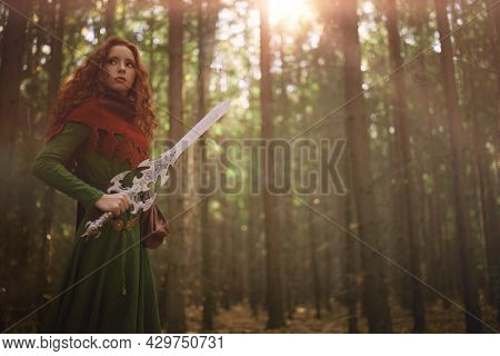 A brave beautiful warrior woman with a sword in a deep forest. Ancient legends. Fantasy world.