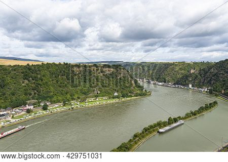 The River Rhine In Western Germany Flows Between The Hills Covered With Forest, Visible Barge And Ro