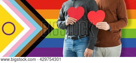 lgbtq, trans and intersex rights concept - close up of male gay couple with red hearts over progress pride flag on background