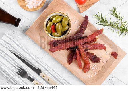 Jerky Meat Strips With Spices, Olives, Rosemary And Beer On Wooden Plate On A Grey Stone Background.