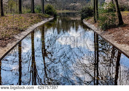 Canal With Mirror Reflection On The Water Surface Of The Blue Sky And White Clouds, Flowing Into A P