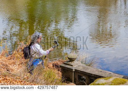 Mature Woman Filming With Her Mobile Phone Gimbal Tripod Head Stabilizer A Lake With Reflection In T
