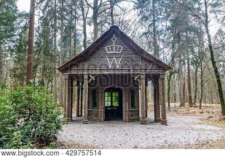 Apeldoorn, Gelderland In The Netherlands. April 19, 2021. Royal Log Cabin With Willemstempel Or Seal