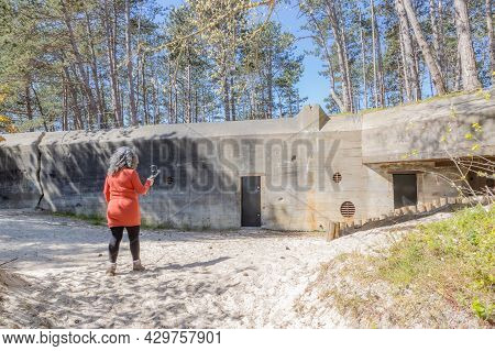 Senior Woman Filming The Ruins Of The Abandoned Wwii Bunker, Called Walvisbunker Because Of Its Whal