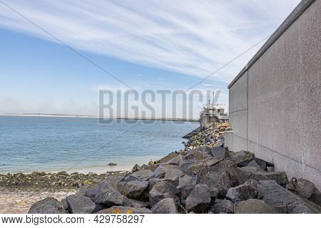 Stones Next To A Concrete Wall At The Delta Works, A Set Of Dams, Sluices, Locks, Dykes, Levees, And