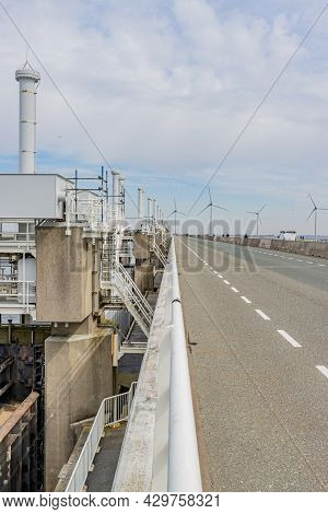 Road Next To Delta Works With Windmills In The Background. Dams, Sluices, Locks, Dykes, Levees, And