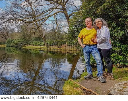 Happy Mature Couple, A Mexican Woman And A Dutch Man Next A Lake Surrounded By Bare Trees And Green